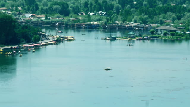vídeos de stock e filmes b-roll de view of the dal lake, near the boulevard road,  with shikaras  and houseboats and also nehru park viewed from pari mahal gardens on top of zabarwan in srinagar - barco casa