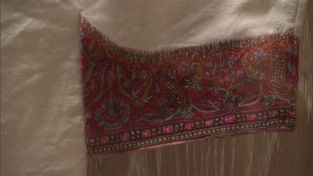 stockvideo's en b-roll-footage met view of the embroidered paisley patterns and tassles on the sleeve of a traditional bahraini abaya. - zoom out