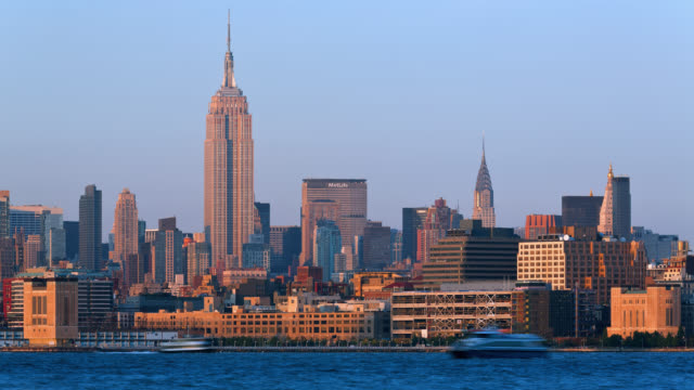 t/l view of the empire state building and the chrysler building as seen from across the hudson river at sunset - empire state building stock-videos und b-roll-filmmaterial