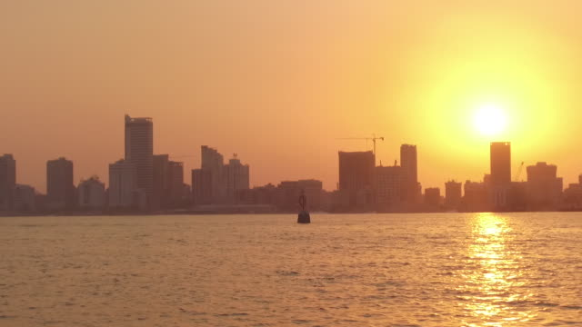 view of the fiery yellow orb of the sun shining over manama at sunset. - heat stock videos & royalty-free footage