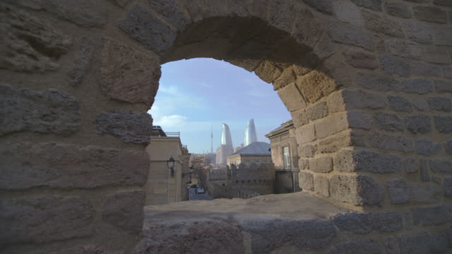 view of the flame towers through a stone window frame in the old city of baku. - window frame stock videos and b-roll footage