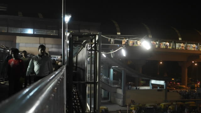 A view of the foot bridge over the busy road at the Chhatarpur metro station in time lapse