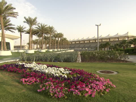 view of the formula one circuit grandstand seen from a landscaped garden full of palm trees cactuses and a bed of flowers - cactus icon stock videos & royalty-free footage
