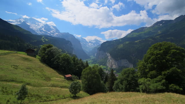 view of the glacial valley of lauterbrunnen with lauterbrunnen village, the jungfrau mountain and the staubbach waterfall. - ethereal stock videos & royalty-free footage