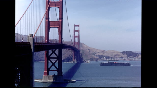 vídeos de stock, filmes e b-roll de / view of the golden gate bridge / closer view showing the rust red tone / ship going underneath bridge golden gate bridge in san francisco on... - imagem tonalizada