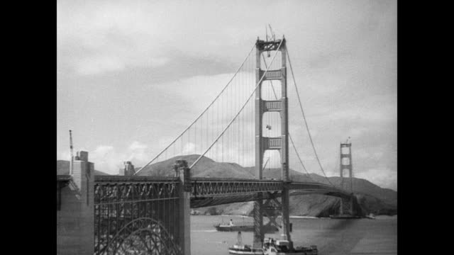/ view of the golden gate bridge / officials and crowd standing around / official holds up final spike to complete the bridge / worker holds up spike... - 1937年点の映像素材/bロール