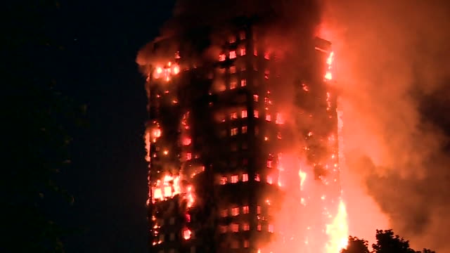 vídeos de stock e filmes b-roll de view of the grenfell tower engulfed by fire at night - inferno fogo
