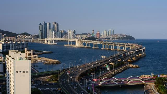 view of the gwangan bridge(it is the longest bi-level bridge over the ocean in korea) with cityscape in haeundae, busan - busan stock videos & royalty-free footage