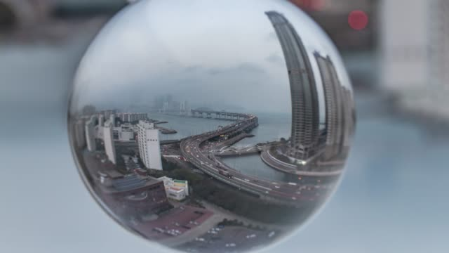 view of the gwangandaegyo bridge(it is the longest bi-level bridge over the ocean in korea) reflected in the glass bead - crystal ball stock videos & royalty-free footage