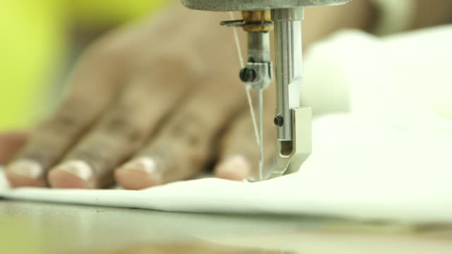 view of the hands of a tailor using an electric sewing machine to stitch a thobe. - maßkonfektion stock-videos und b-roll-filmmaterial
