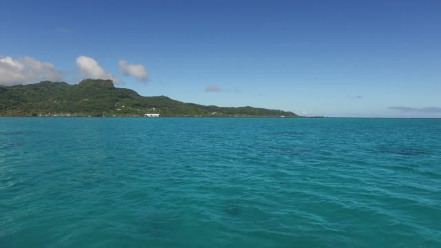 view of the lagoon with sky and mountains - isola di tahaa video stock e b–roll