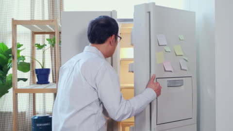 view of the man watching an empty refrigerator and thinking some problems - vorderansicht stock-videos und b-roll-filmmaterial