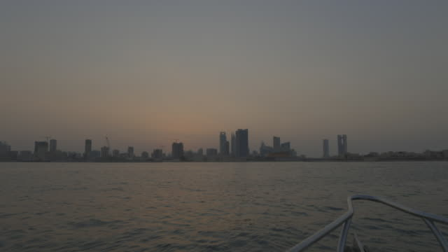 view of the manama skyline at sunset from a boat. - ペルシャ湾点の映像素材/bロール