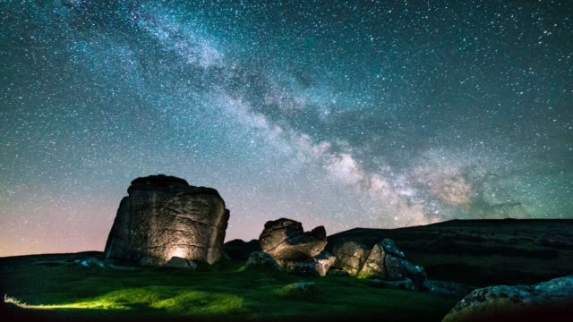 view of the milky way over the illuminated natural granite rock formations of bonehill rocks in dartmoor national park, devon, england. the image has... - beauty in nature stock videos & royalty-free footage