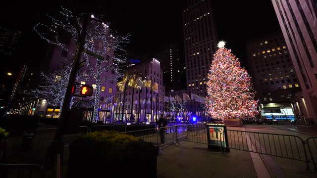 view of the newly lit christmas tree reflected off a nearby wall at rockefeller center on december 03, 2020 in new york city. - rockefeller center christmas tree stock videos & royalty-free footage