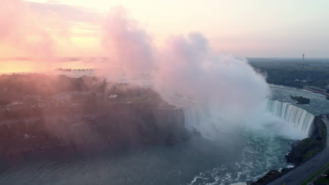 vídeos de stock, filmes e b-roll de view of the niagara falls(horseshoe falls and bridal veil falls) in ontario, canada and in newyork, usa at sunrise - canadá