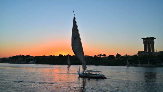 view of the nile river with sailboats at sunset in aswan, egypt - river nile stock videos & royalty-free footage