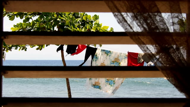 view of the ocean and drying rack through a window with colonial style sun shutter, cuba - drying rack stock videos and b-roll footage