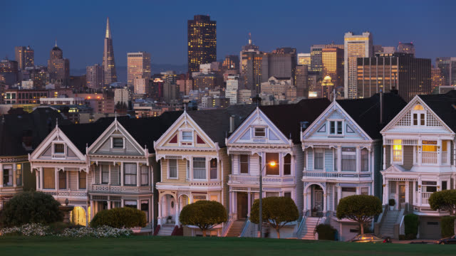 t/l view of the painted ladies near alamo square with city skyline in the background at dusk / san francisco, california, usa - san francisco california stock videos and b-roll footage