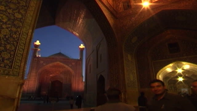 view of the portal of the safavid era shah mosque with lit minarets and dome from one of the decorated symmetrical arcades in the inner courtyard at... - shi'ite islam stock videos & royalty-free footage