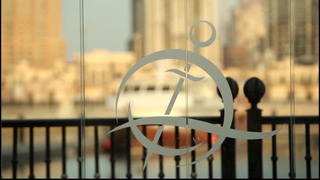 view of the porto arabia residential complex logo etched on a window showing a view of the marina and towers of pearl island. - doha stock videos & royalty-free footage