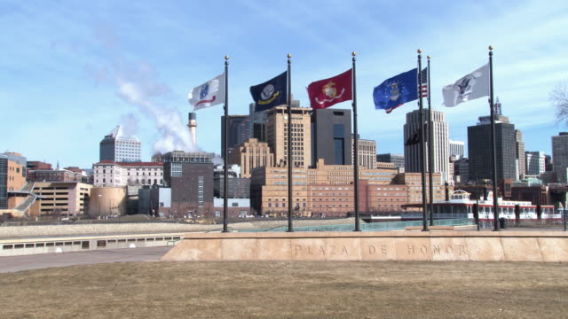 a view of the st. paul skyline with flags of the armed forces in the foreground - saint paul stock-videos und b-roll-filmmaterial