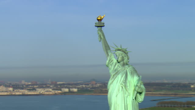 ms pan zo view of the statue of liberty with manhattan skyline in background / new york city, new york, usa - statue of liberty new york city stock videos & royalty-free footage