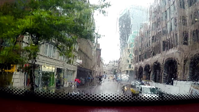 View of the streets of London from a London bus on a rainy day.