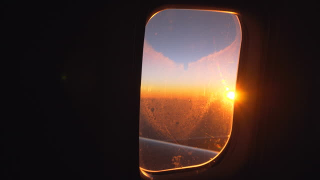 View of the sunrise from airplanes window during the flight
