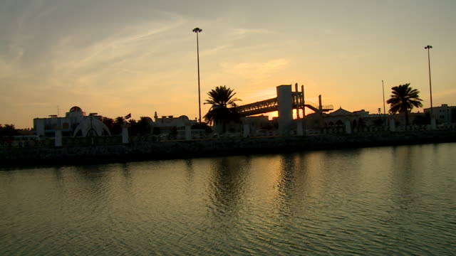 view of the sunset from one of abu dhabi's salt water canals. - ペルシャ湾点の映像素材/bロール