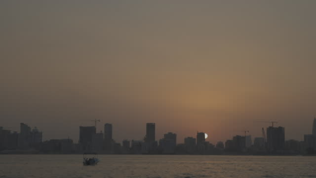 view of the sunset throwing the manama skyline into silhouette. - ペルシャ湾点の映像素材/bロール