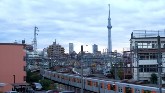view of the tokyo skyline during sunrise with a train and tokyo skytree in background. - rail transportation stock videos & royalty-free footage