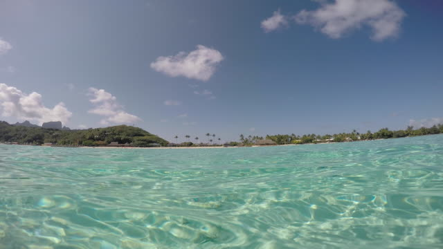 stockvideo's en b-roll-footage met view of the transparent sea of the bora bora lagoon with in the background the beach, the coconut trees and the hills - polinesische cultuur