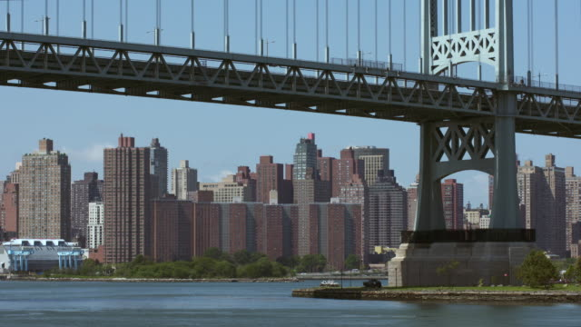 View of the Upper East Side along FDR Drive from Astoria Park. Traffic moves along the RFK Bridge above the East River.