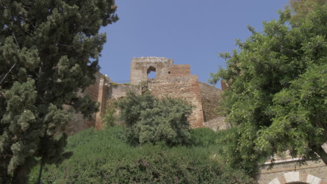 view of the walls of alcazaba from jardines de pedro luis alonso, malaga, andalucia, spain, europe - circa 11th century stock videos and b-roll footage