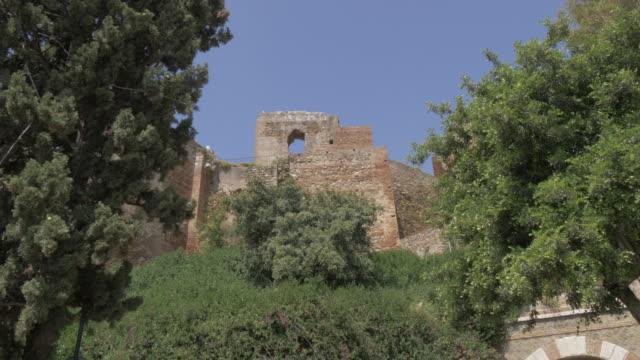 vídeos de stock e filmes b-roll de view of the walls of alcazaba from jardines de pedro luis alonso, malaga, andalucia, spain, europe - por volta do século 11 dc