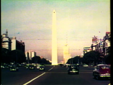 1953 WS View of the widest street in the world, people outside fountain / Buenos Aires, Argentina / AUDIO