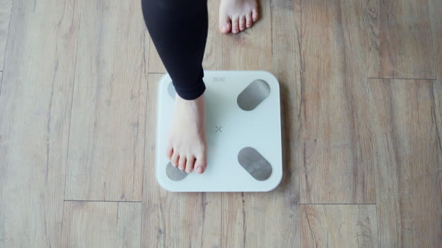 view of the woman stepping on the scale - waage gewichtsmessinstrument stock-videos und b-roll-filmmaterial