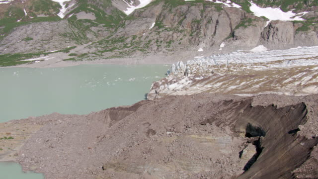 vidéos et rushes de ms aerial pan view of thermal hot pool and cracks in snow at fourpeaked mountain range and glacier / alaska, united states - piscine thermale