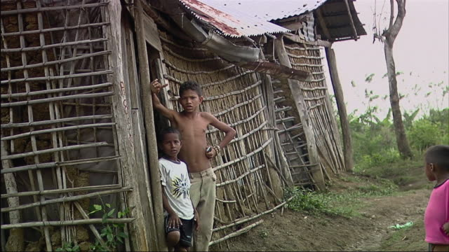 vídeos de stock e filmes b-roll de ms view of three boys in front of hut / colombia  - mill