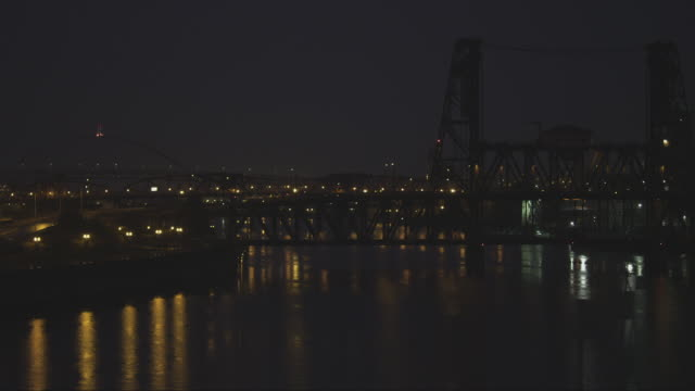 WS View of Three bridges of Freemont, Broadway and Steel bridge cross Willamette River in Portland, Oregon at night on rainy day / Portland, Oregon, United States