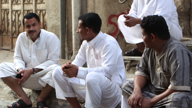 view of three saudi men, chatting, sitting on a pavement, looking into the camera, in al-balad, the historic centre of jeddah. - jiddah stock videos & royalty-free footage