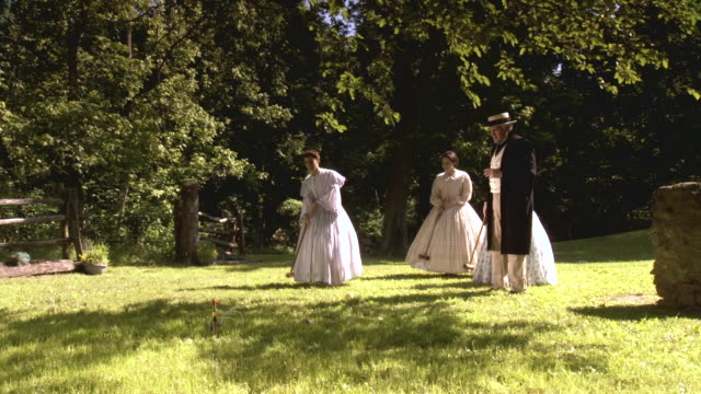 WS View of Three women and man play croquet on grassy field / Middleburg, Virginia, United States