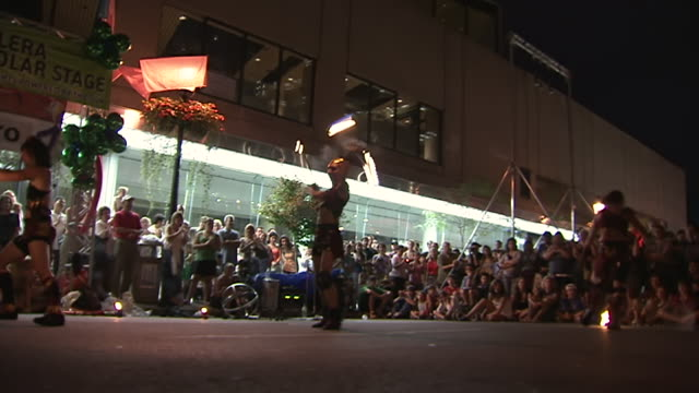 ms zo zi view of three women performing acrobatics tricks while holding fire torches at busker fest / toronto, ontario, canada - street performer stock videos and b-roll footage
