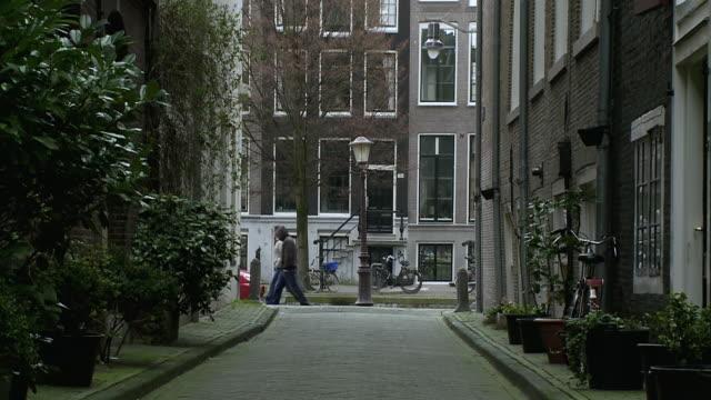 WS View of Through alleyway, people walking past / Amsterdam, Holland