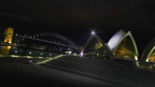 vídeos de stock, filmes e b-roll de ws tu t/l view of thunderstorm with lightning above the sydney opera house and bridge at night / sydney, new south wales, australia. - relâmpago em ziguezague