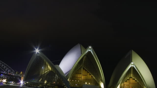 vídeos de stock, filmes e b-roll de ws td t/l view of thunderstorm with lightning above the sydney opera house and bridge at night / sydney, new south wales, australia. - relâmpago em ziguezague