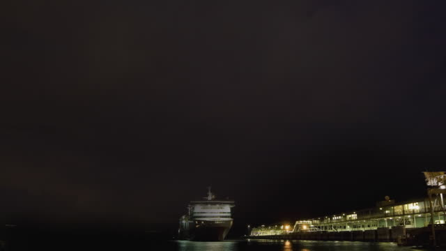 WS TU PAN T/L View of thunderstorm with lightning over docks, ferry departs / Melbourne, Victoria, Australia.