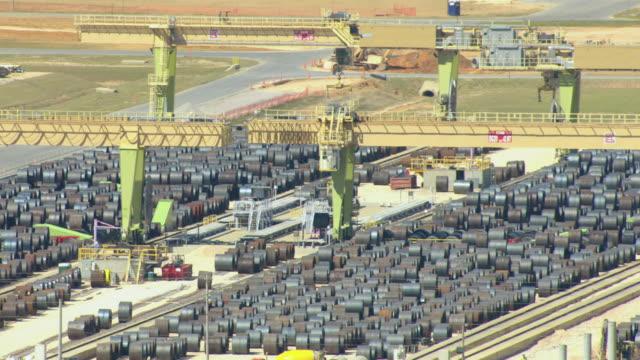 vídeos y material grabado en eventos de stock de ws aerial view of thyssenkrupp steel plant in washington county and rolling cranes lifting steel cylinders / alabama, united states - fundición de acero