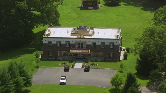ws aerial pov view of tibetan mongolian buddhist center with kumbum chamtse ling interfaith temple / monroe county, indiana, united states - temple building video stock e b–roll